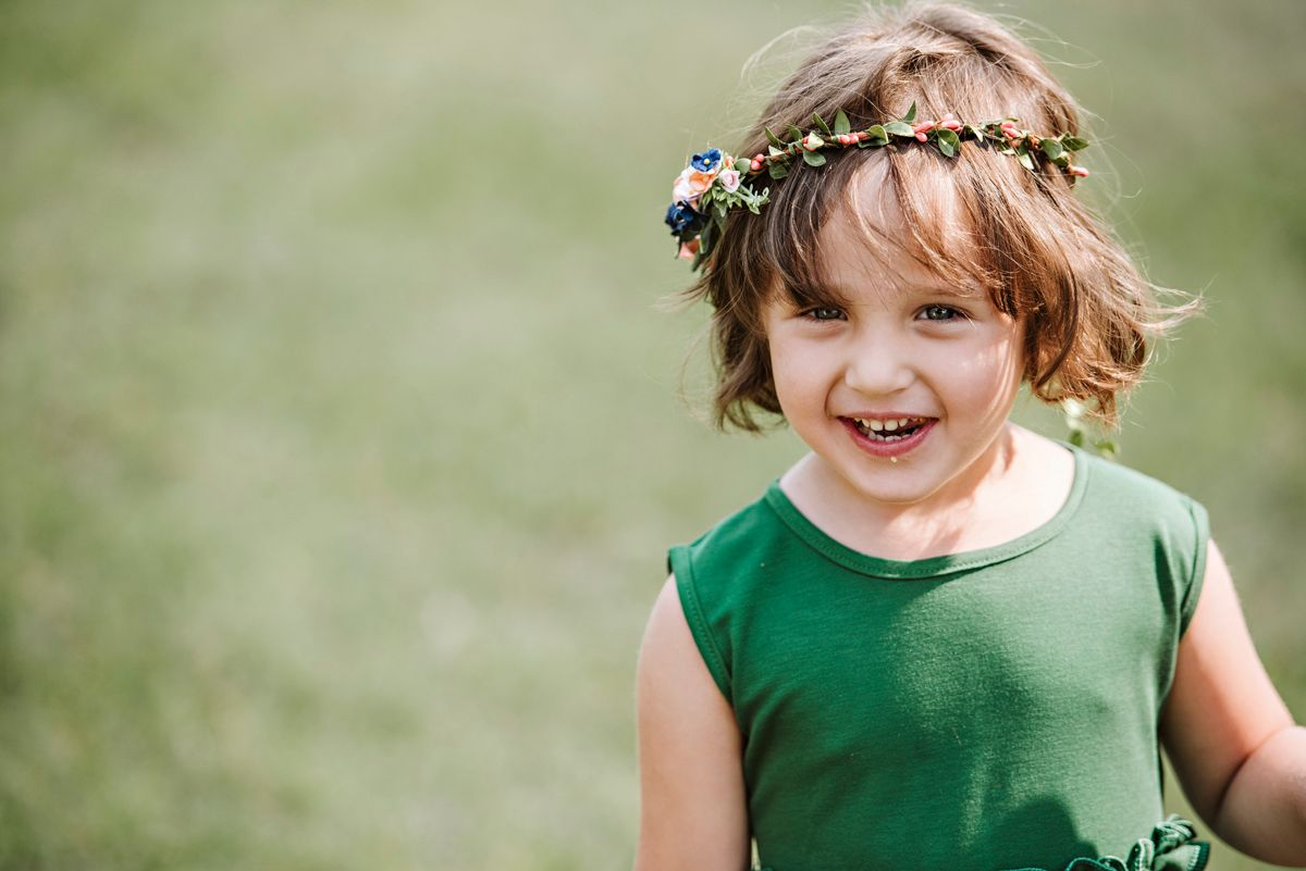 Flower girl in an emerald dress and flower crown laughs
