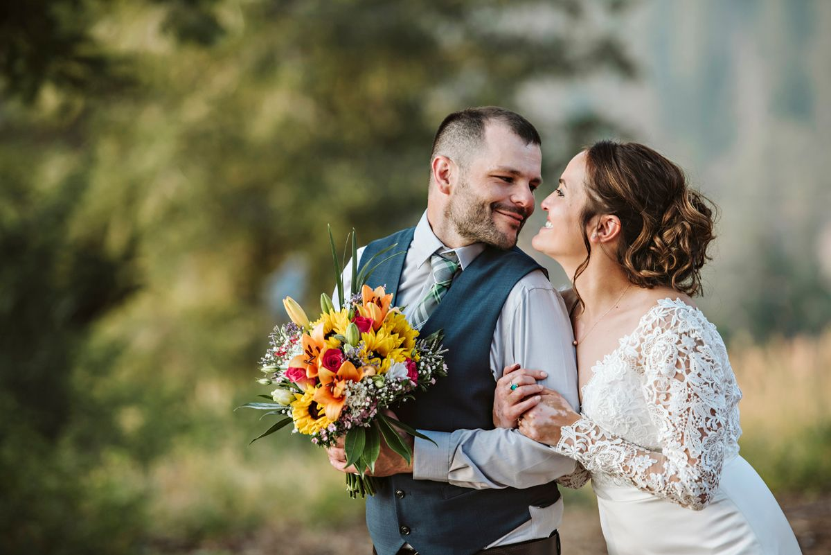 Groom holds bouquet as couple cuddle