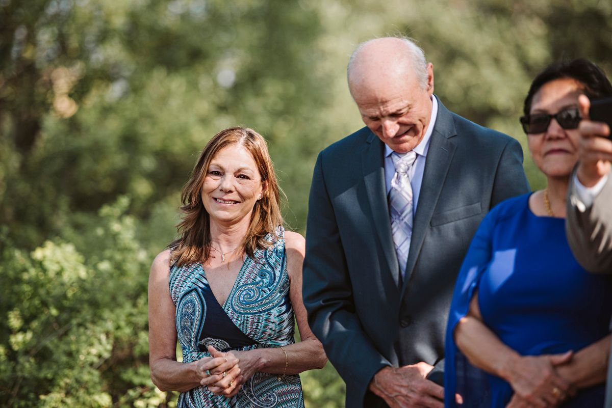 Groom's mother and grandpa smile at wedding