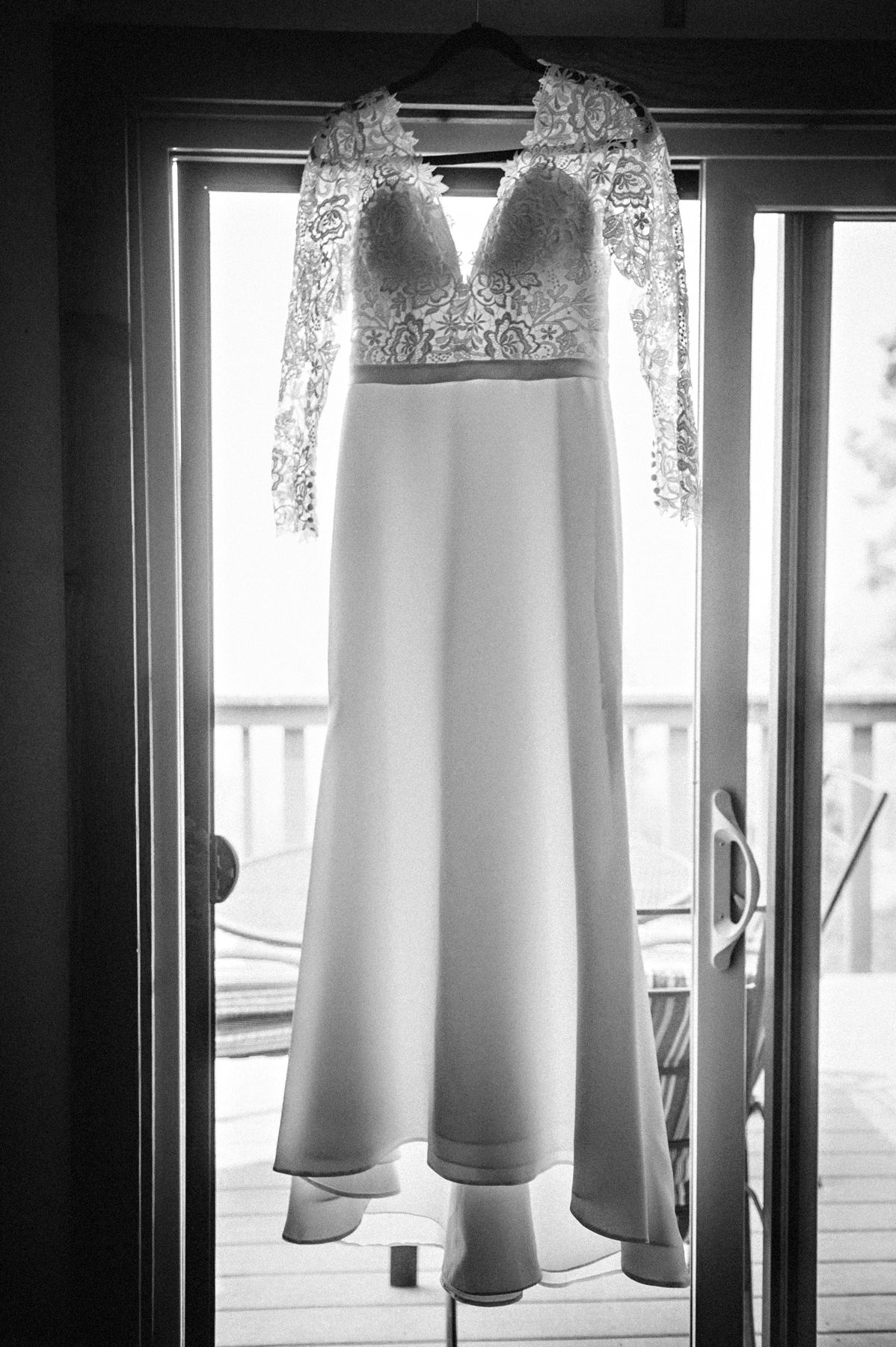 Black and white photo of bride's dress hanging