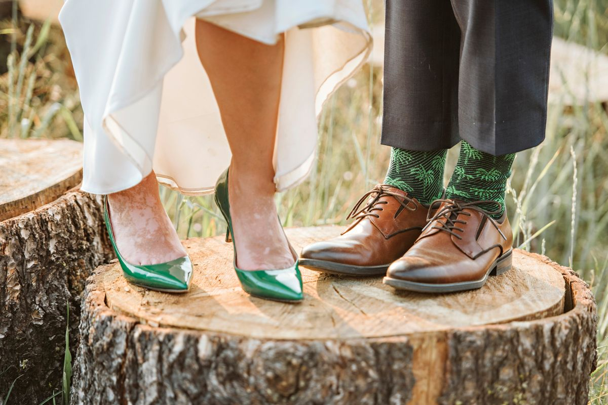 Bride and groom show off their wedding shoes