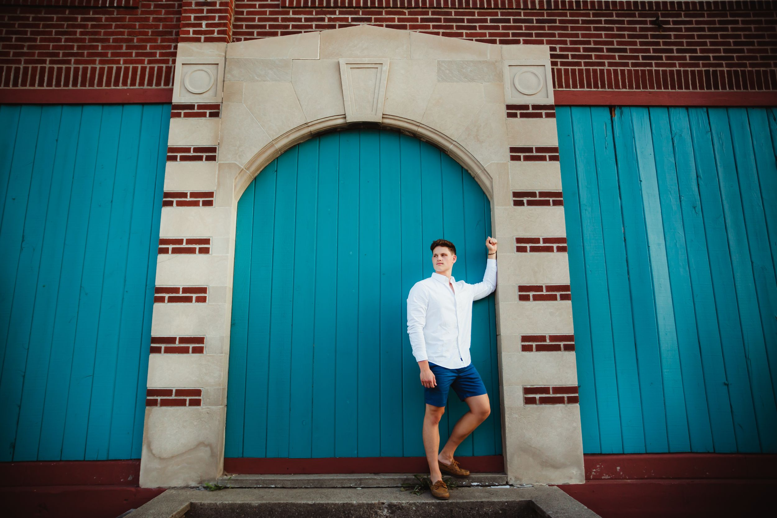 Wide shot of high school boy standing on a step and leaning against a concrete pillar. The wall is brick and teal wood.