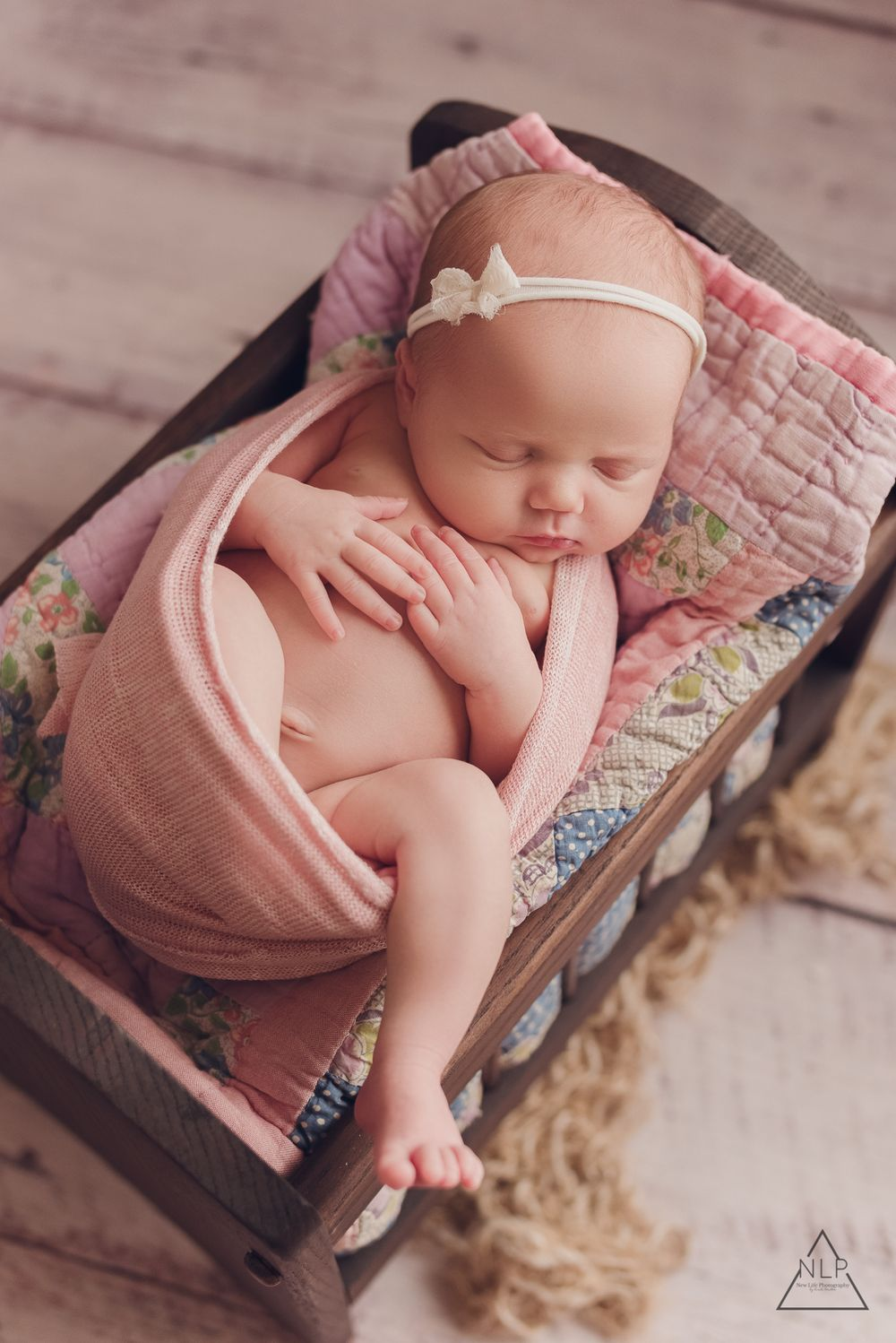 baby girl on a pink quilt, in a prop bed