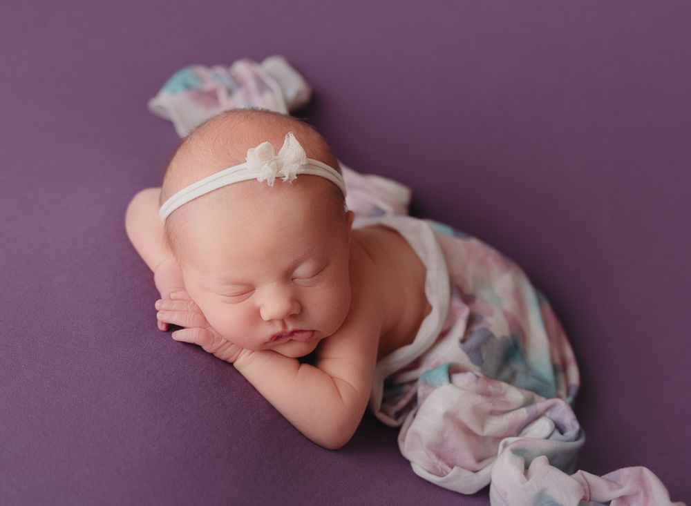 baby girl posed on purple with floral wrap draped over the back