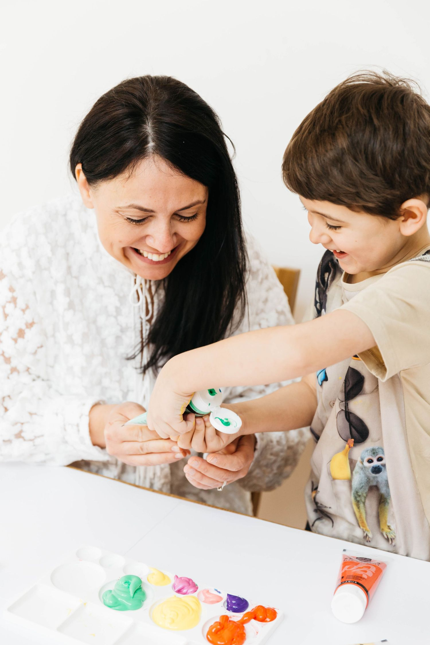 mum with dark hair squeezing paint with son smiling