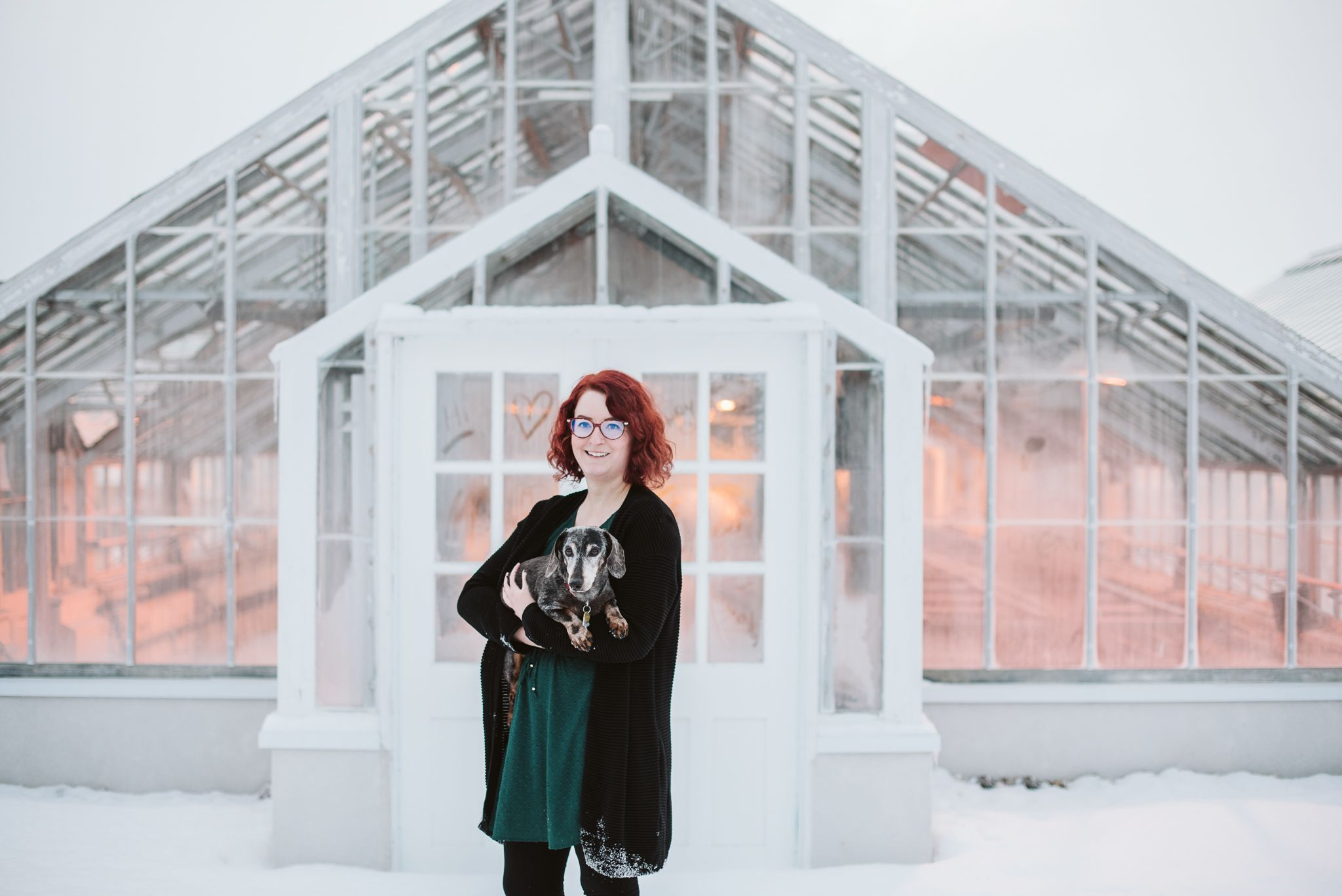valerie miles photography young woman with red hair holding a senior black and tan dachshund in front of a greenhouse