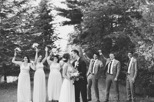 bride and groom in the foreground with their wedding party standing behind them cheering at bean town ranch ottawa