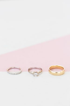 macro shot of 3 wedding bands on a white and pink surface ottawa wedding photographer