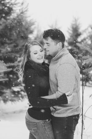 young couple embracing during snowfall at a tree farm in winter