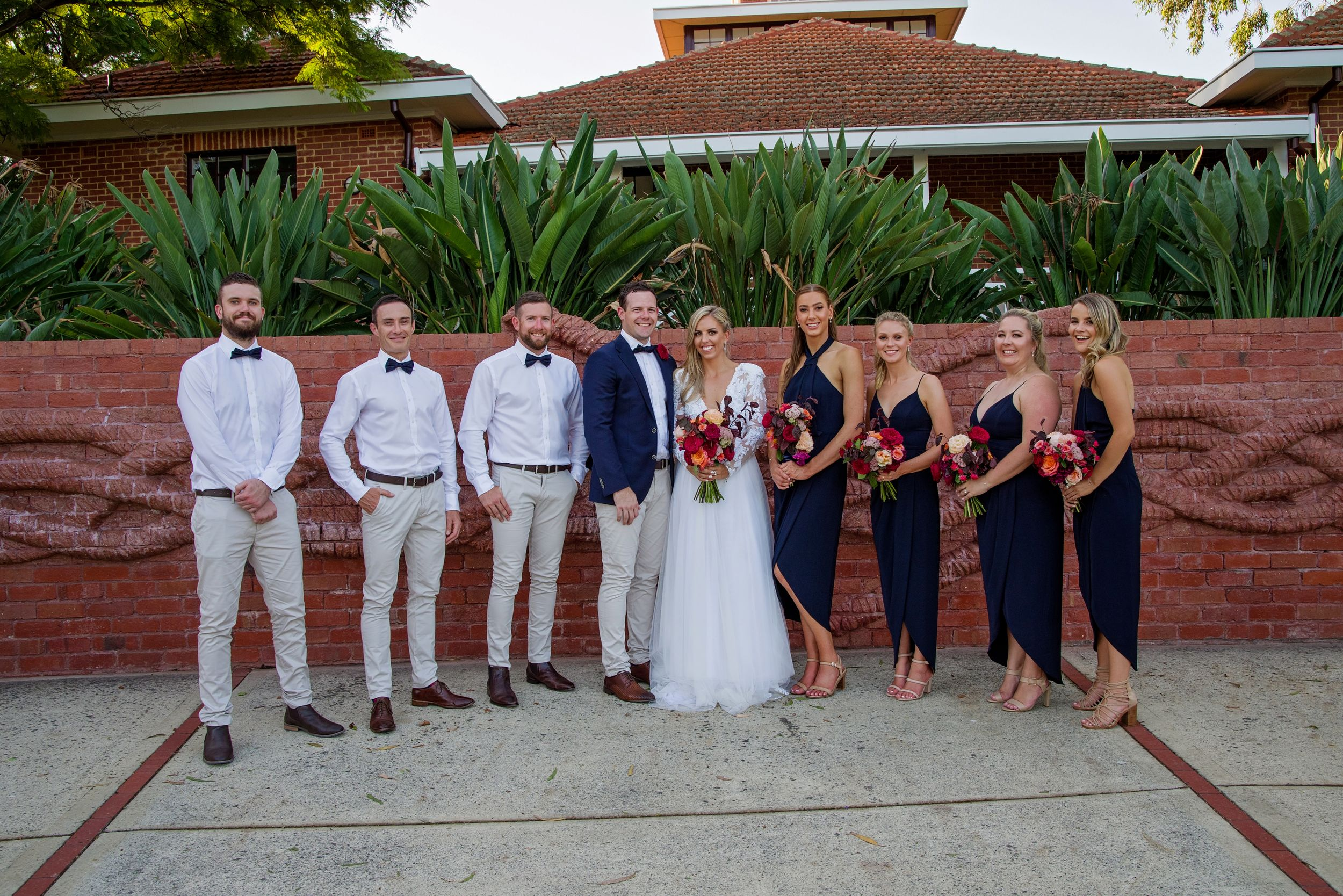bridal party in a line smiling at camera at Heathcote Reserve Perth