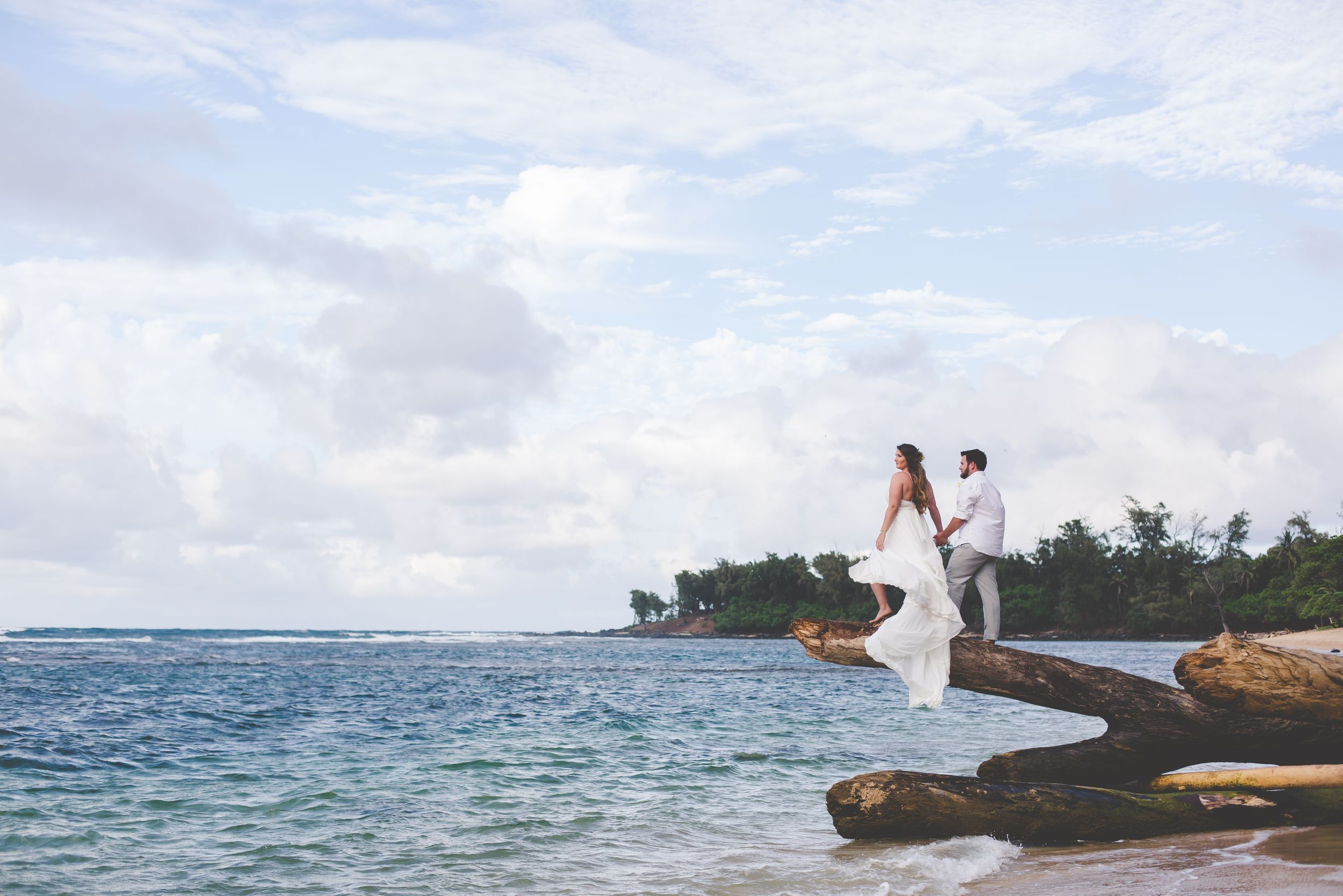 Wide photo of bride and groom standing on the end of a large lot hanging out over the ocean. Big blue sky with clouds