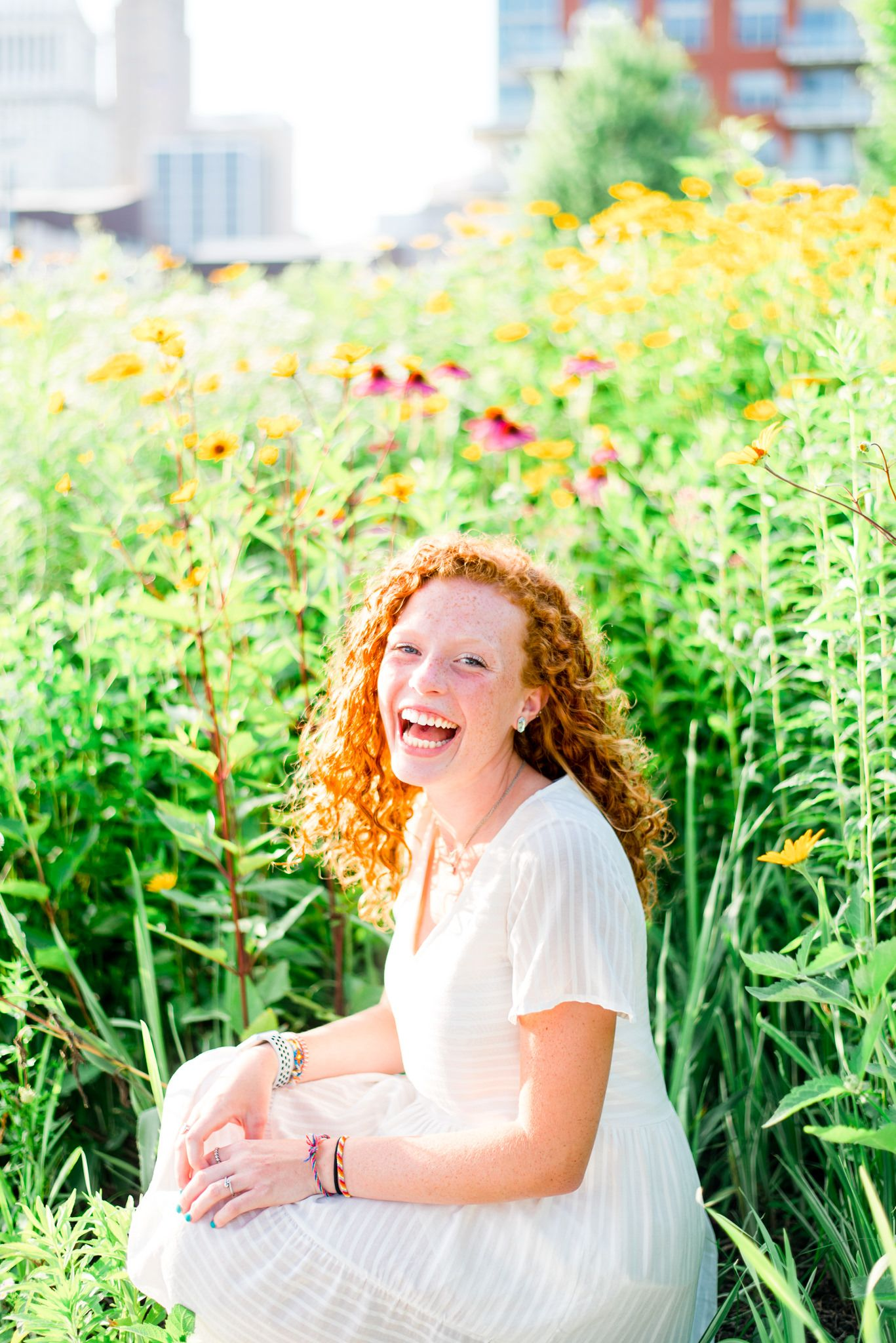 young woman with curly red hair laughing widely in the yellow and pink flowers at Smale Park at sunset