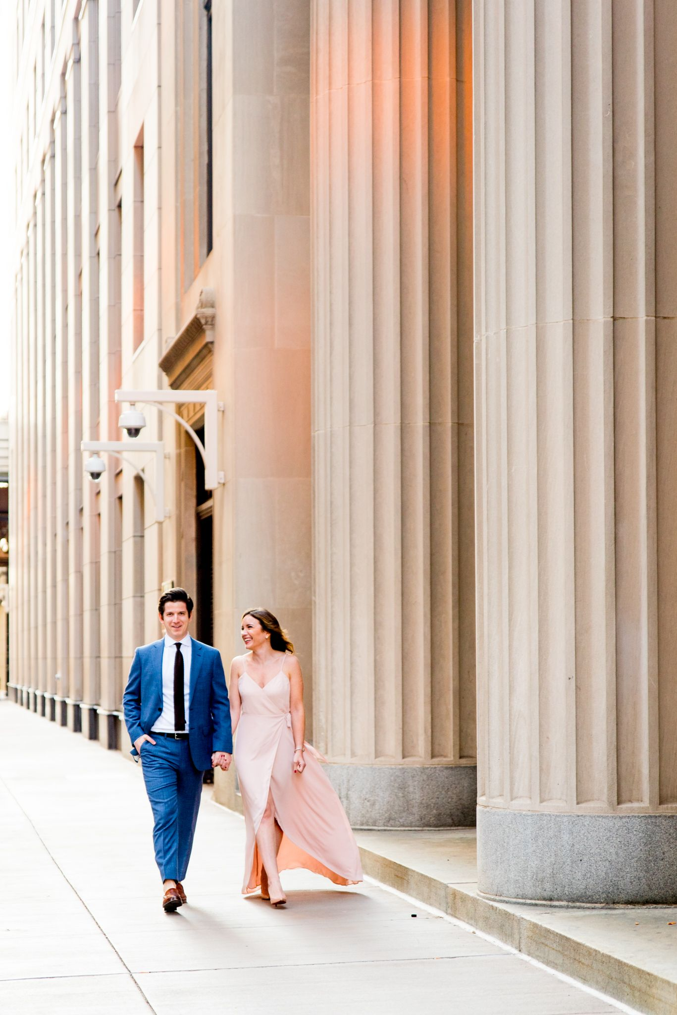young engaged man and woman holding hands smiling and walking near Chicago Board of Trade