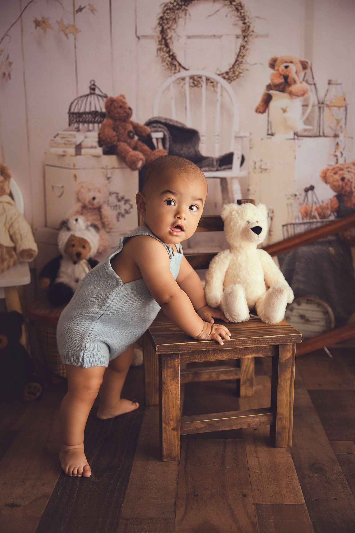 baby holding on to a chair to stand up blue romper