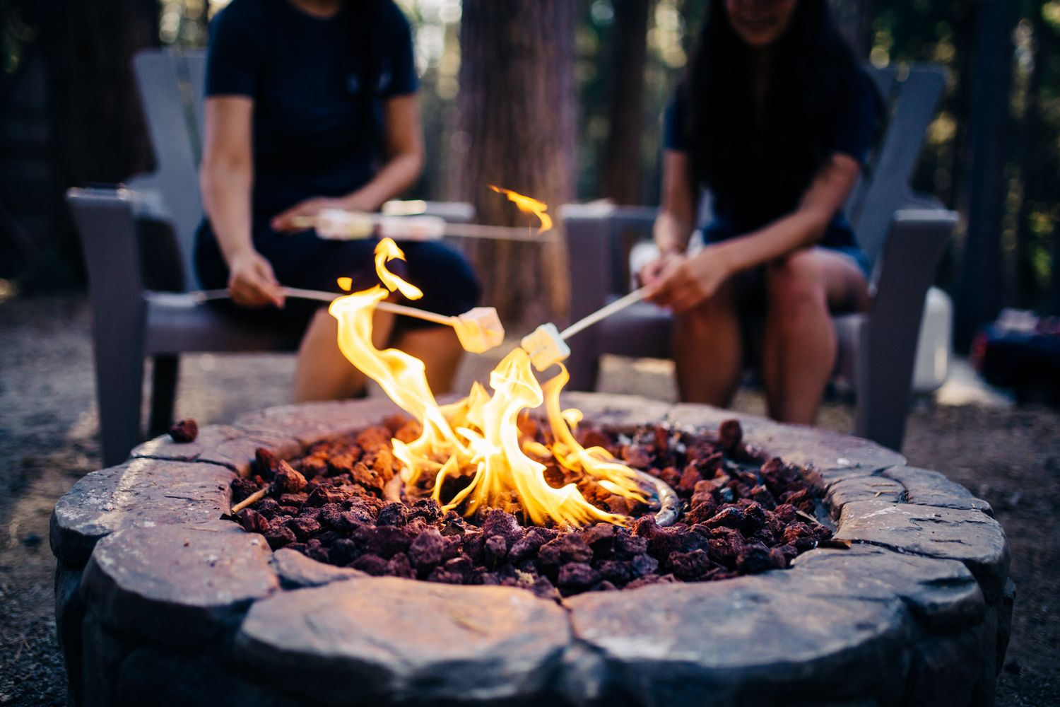 girls around fire pit at the inn town campground