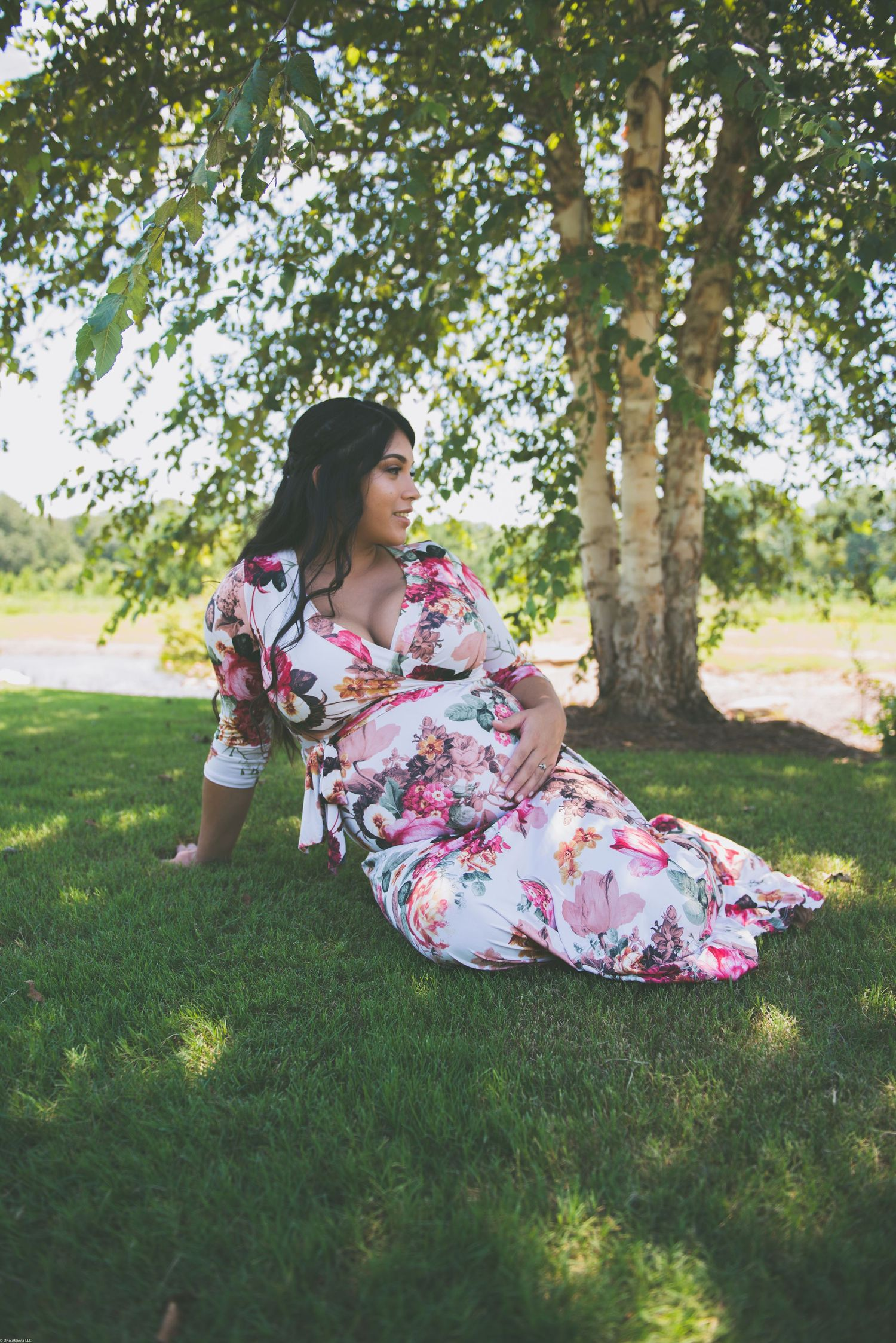 Pregnant mother in flowery dress on grass