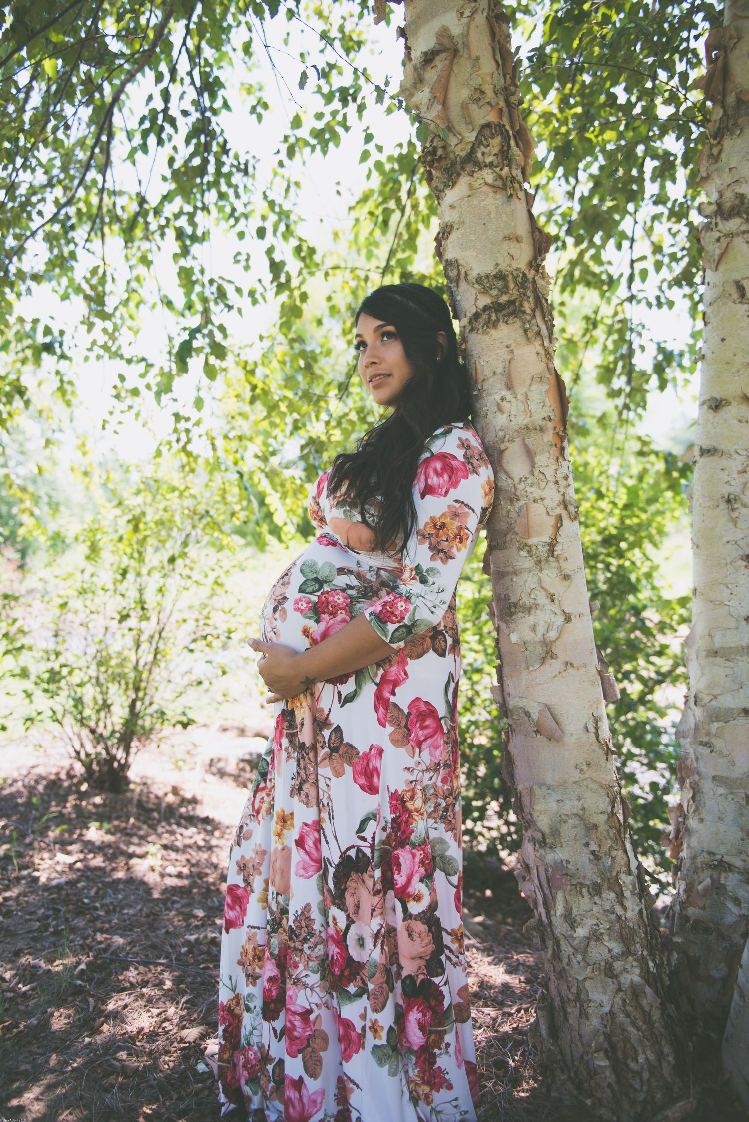 Pregnant mother in flowery dress on tree