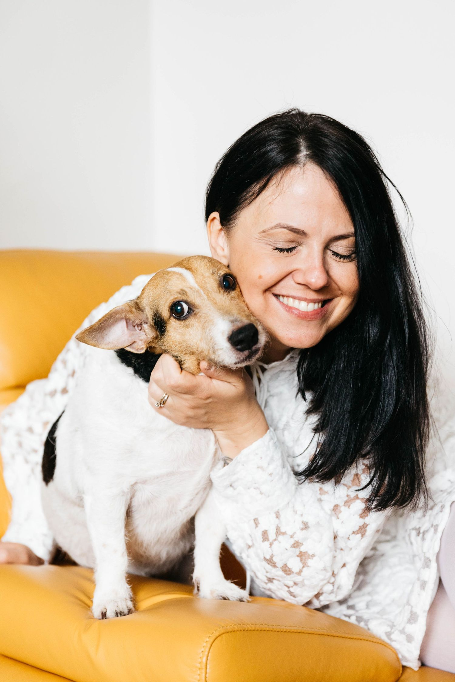 woman with dark hair in white dress cuddling white brown dog