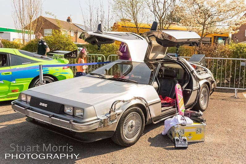 stars and cars wide shot of the back to the future delorean with the gull wing doors open