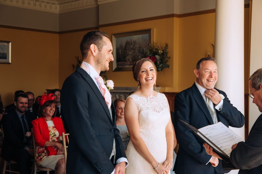 Zara Davis Wedding Photography Near Stroud, Gloucestershire, Cotswolds Glenfall House laughing at the alter