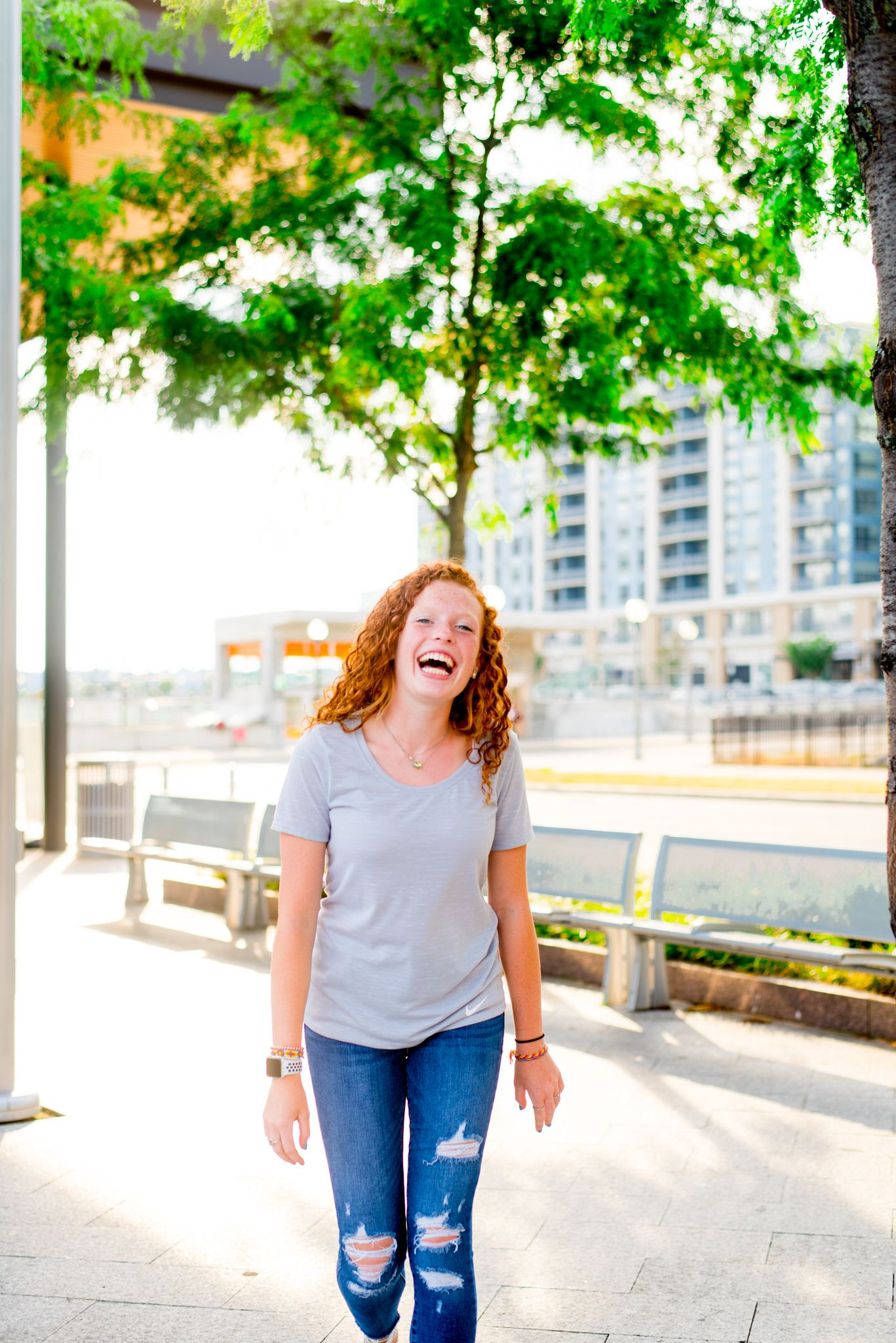young woman laughing in front of tree at sunset at Smale Riverfront Park in CIncinnati for senior pictures