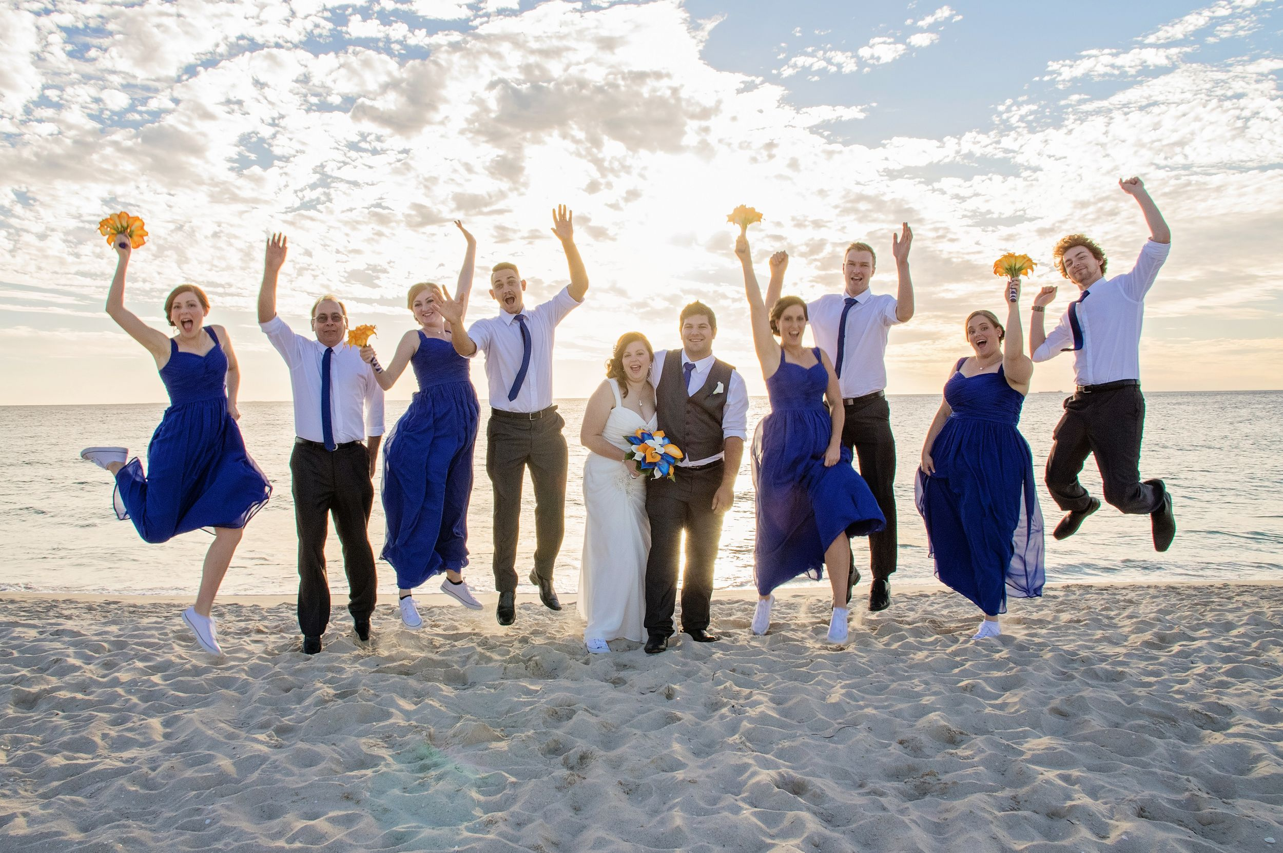 fun photo of bridal party jumping in the air at the beach