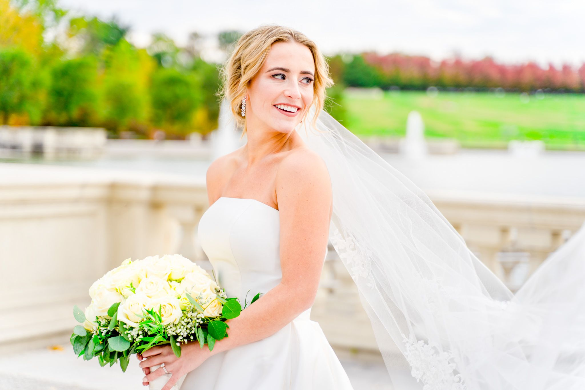 blonde bride with updo and long veil and white bouquet looking over her shoulder in Forest Park wedding pictures