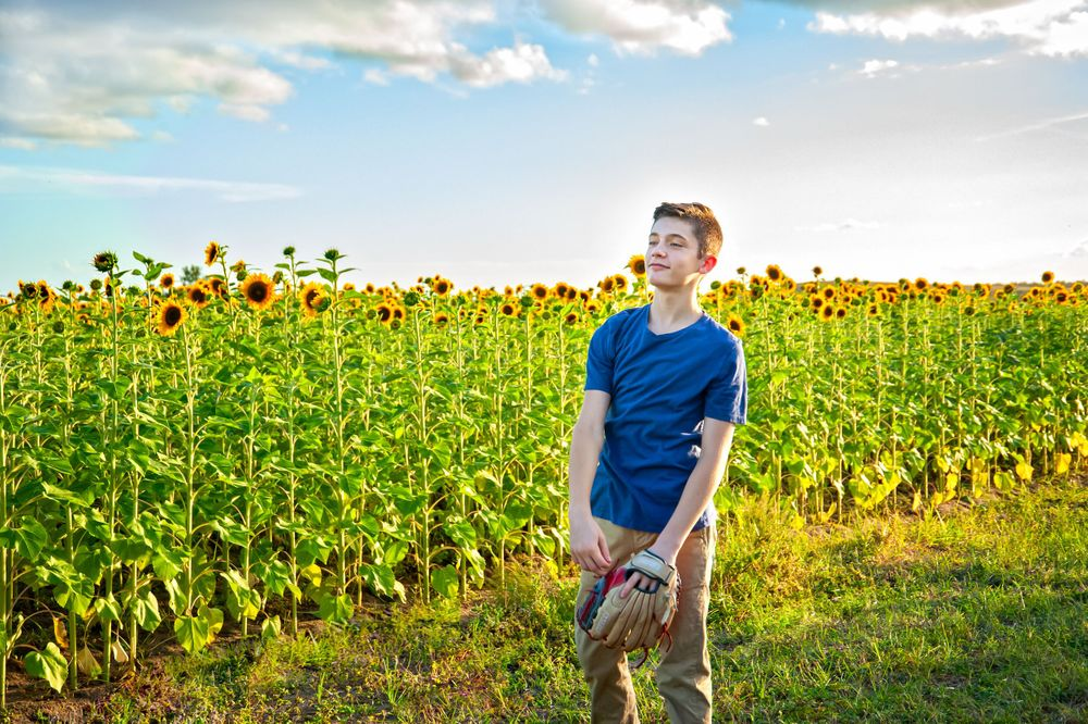 proud young son in sunflower field