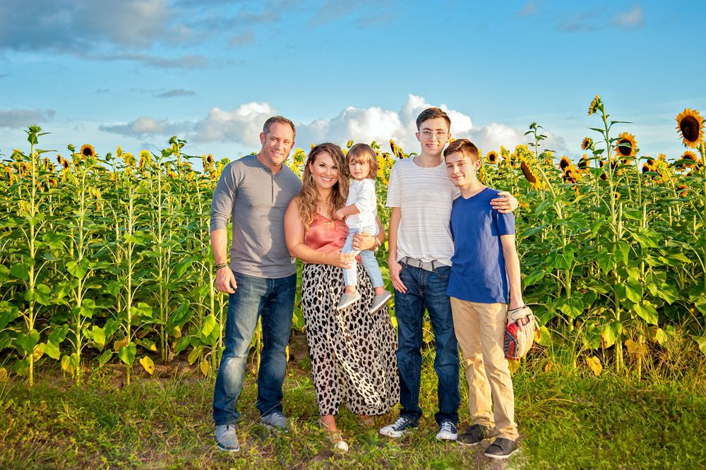 family posing for portrait in sunflower field