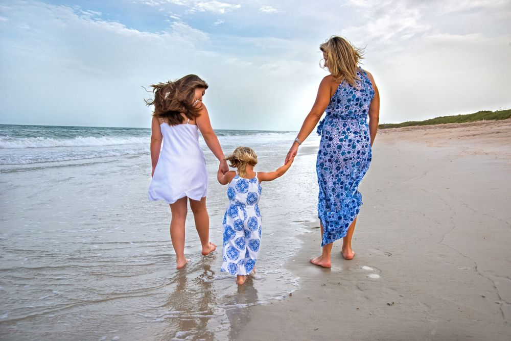 mother and daughters walk along the shore