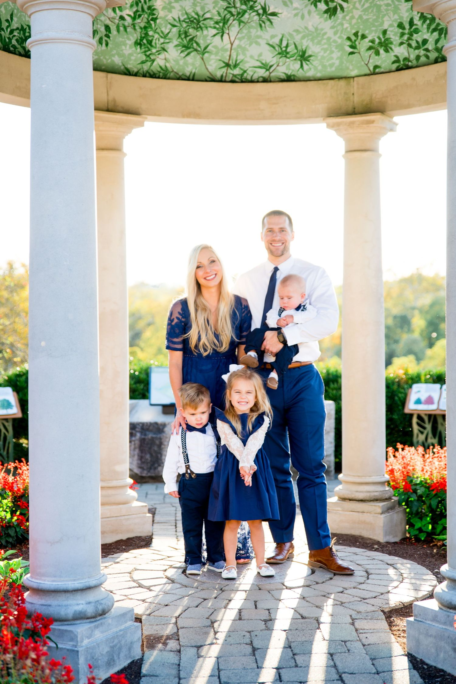 two parents and three young children dresses in white and navy gather in close and smile under a gazebo at sunset