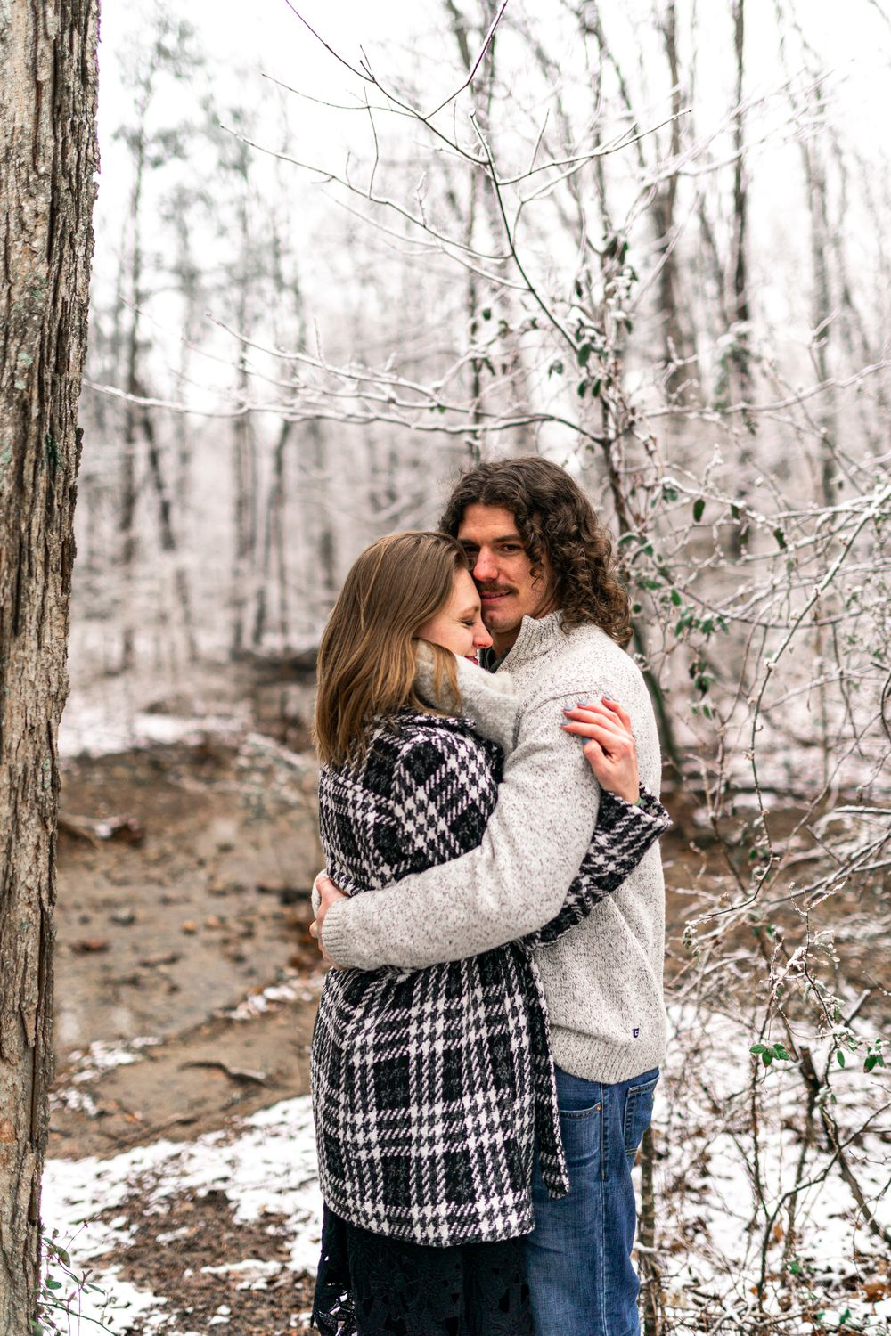 Alex and Chad holding each other in the snowy wilderness at Bernheim Forest in Kentucky
