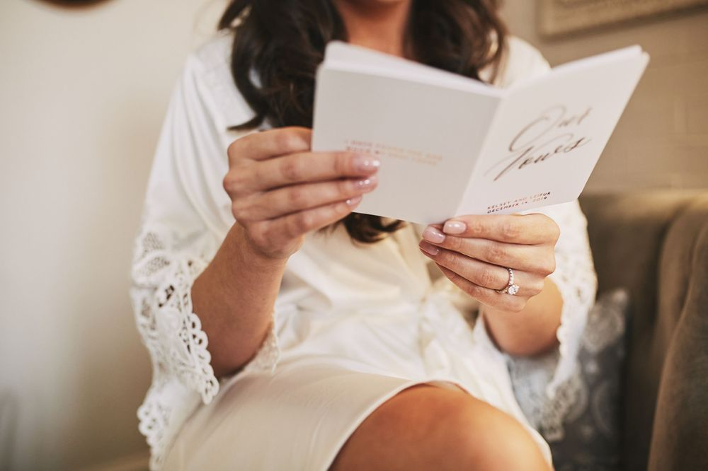 Bride reading her vows in her robe as she prepares for her wedding day