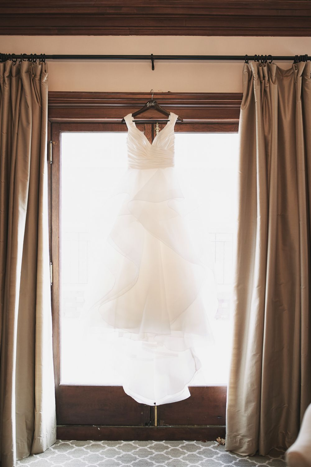 white wedding dress hanging in front of the window