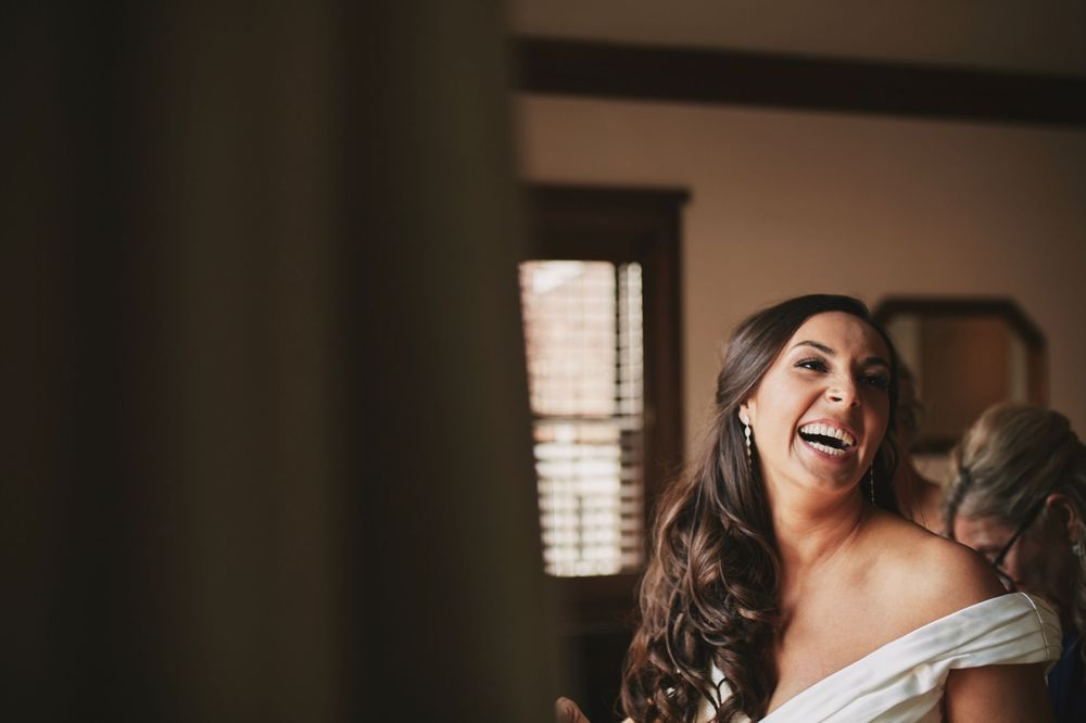 bride laughs with her wedding dress on