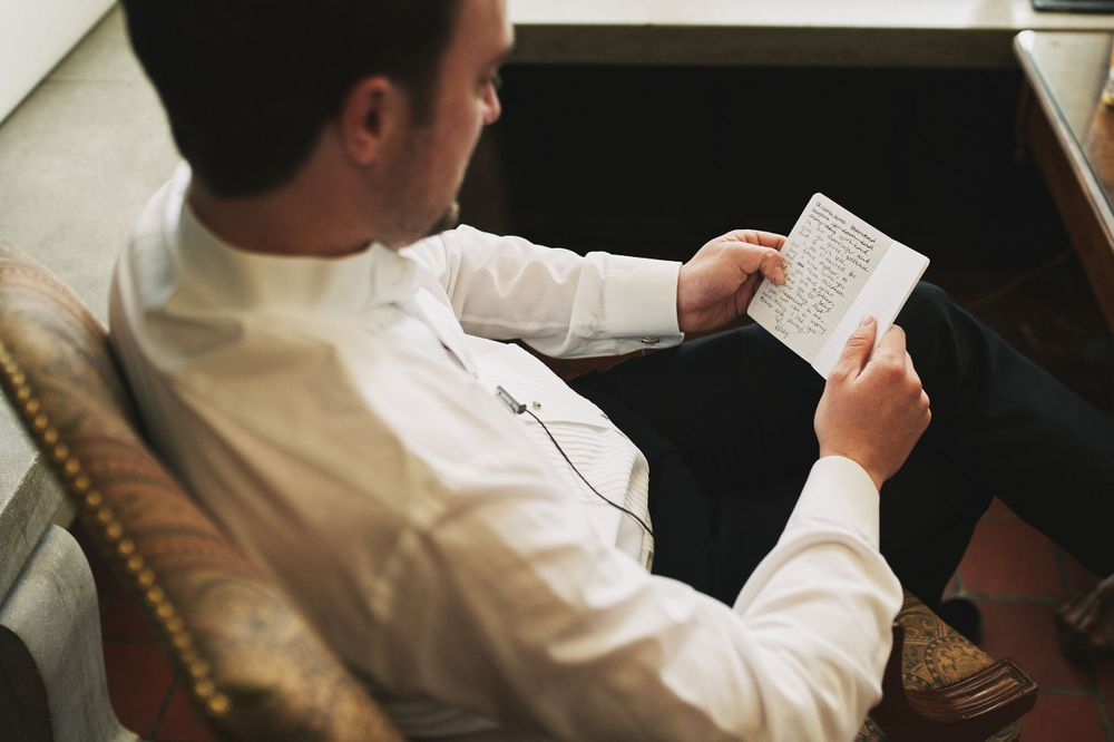 groom reading a letter from his bride before his wedding day