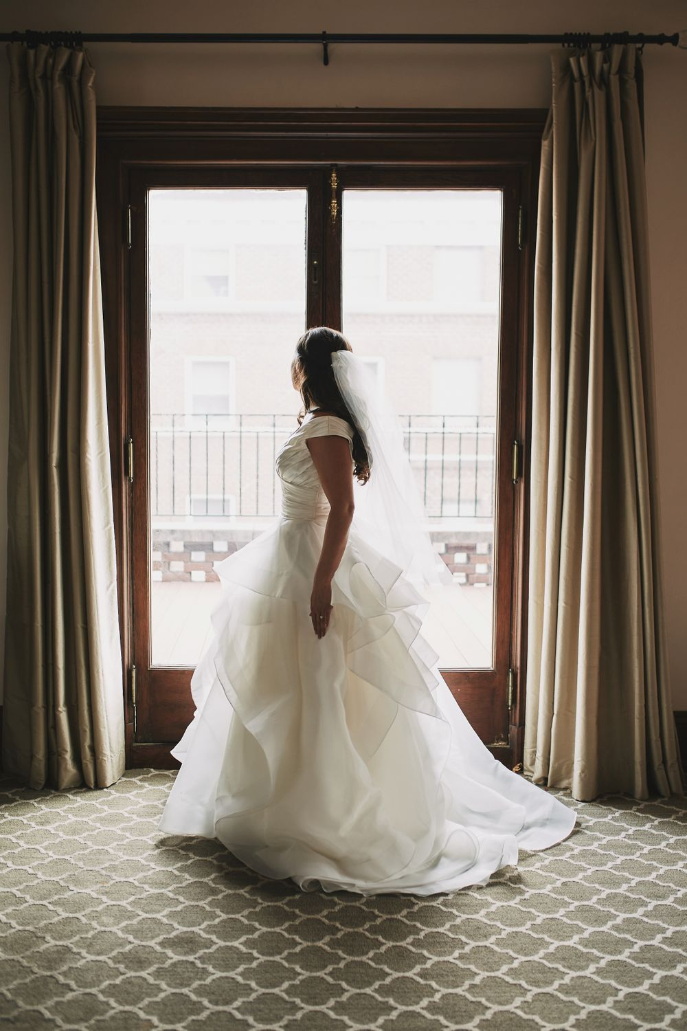 bride in her wedding dress looking out the window