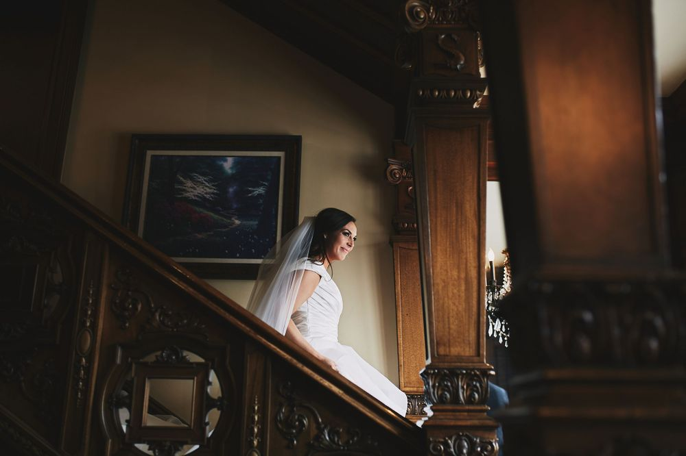bride walks down the stairs in her wedding dress