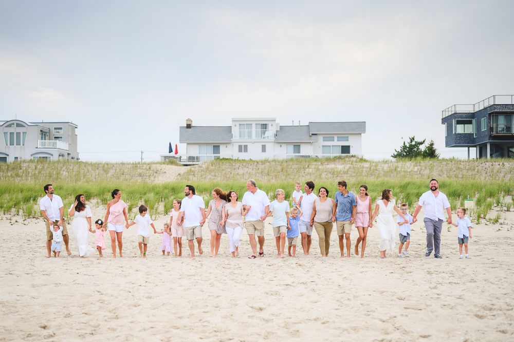 large family walking and holding hands having fun on lbi beach