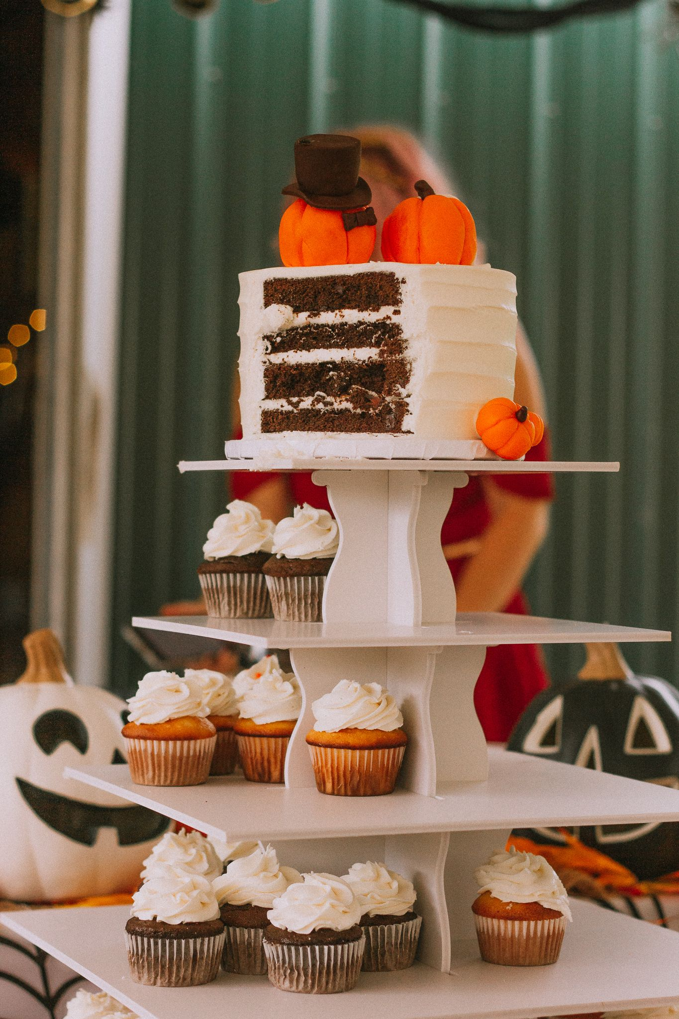 icing pumpkin dressed up as bride and groom on top of simple cake