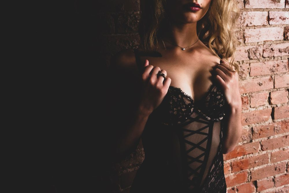GORGEOUS BLONDE WEARING LINGERIE STEPPING OUT OF THE SHADOWS TO SHOW OFF THE LACE OF HER CORSET