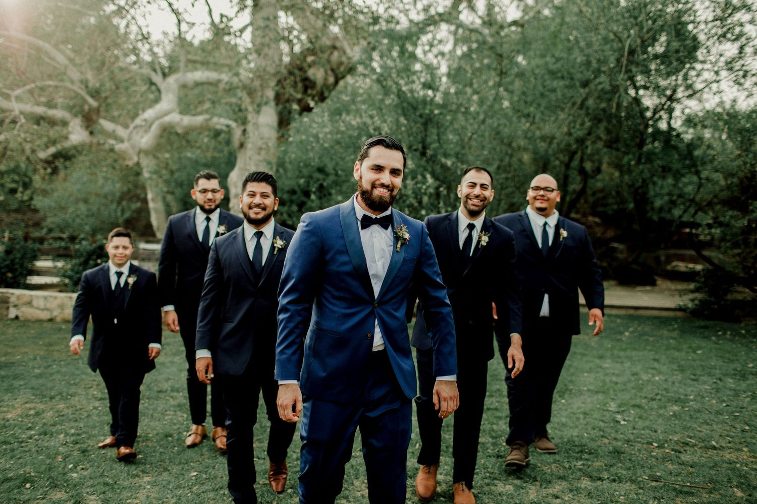 groom and wedding party walking in field
