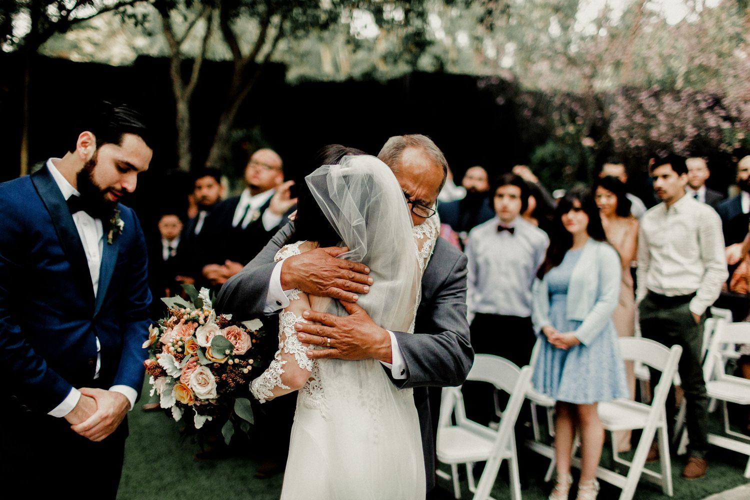 bride giving hug to father as he passes her off