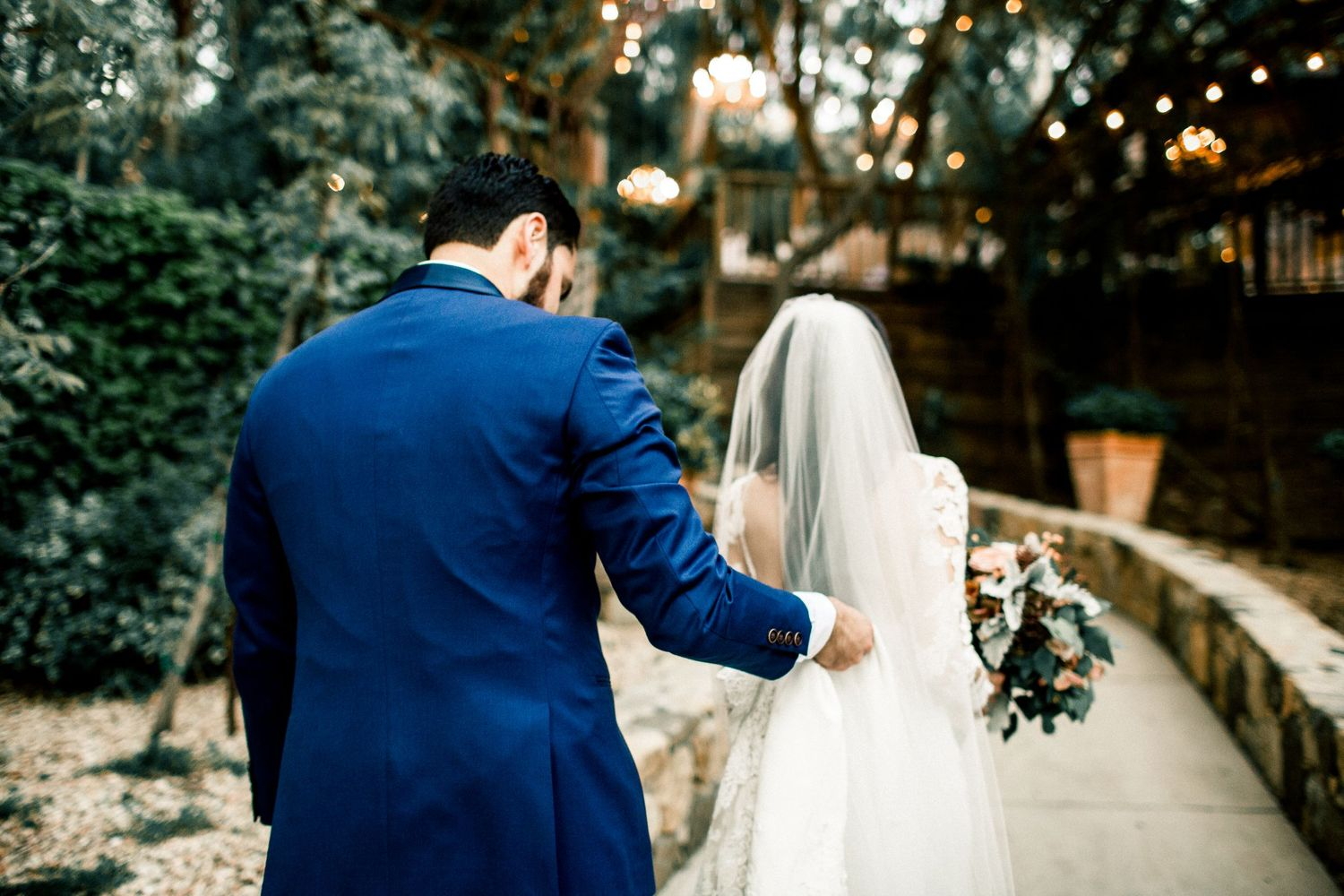 groom helping bride with dress and veil