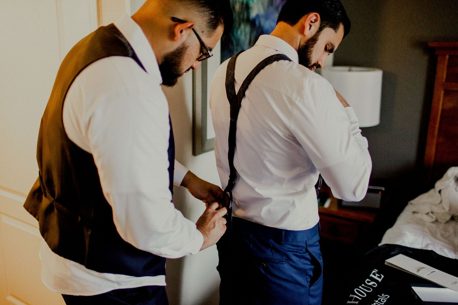 best man helping groom with suspenders at holiday inn