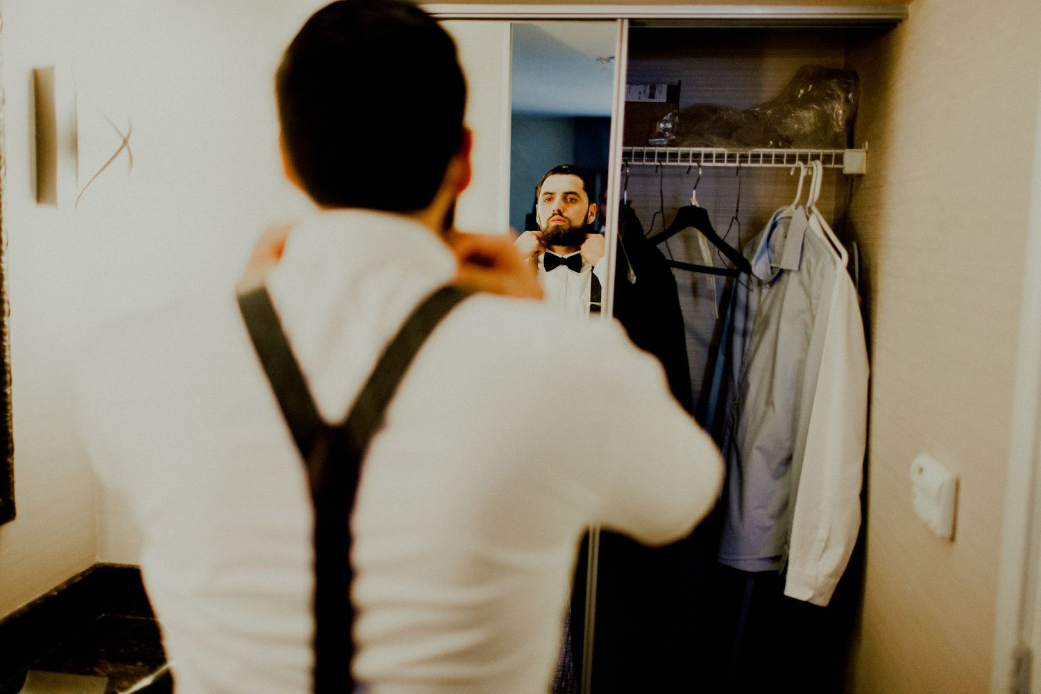 groom adjusting bow tie in front of mirror