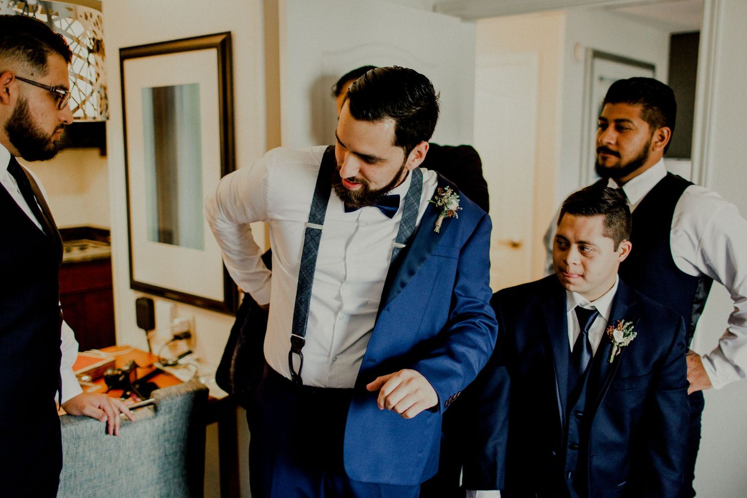 groom putting on blazer jacket with groomsmen watching