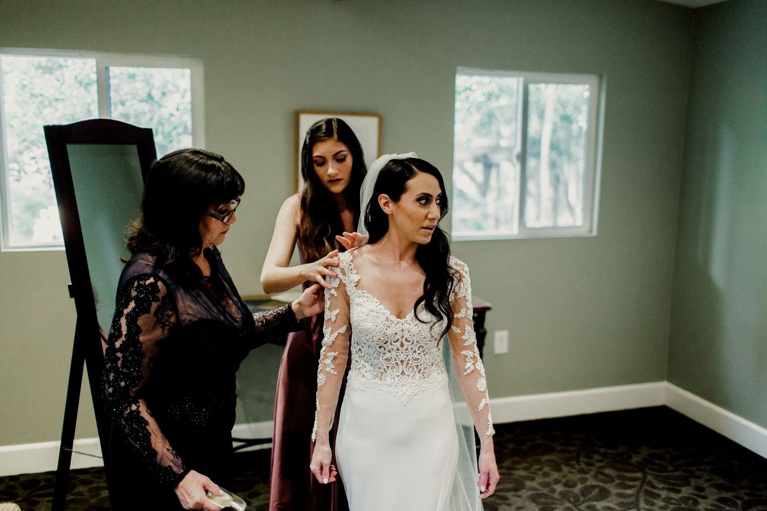 mom and sister helping bride put on wedding dress