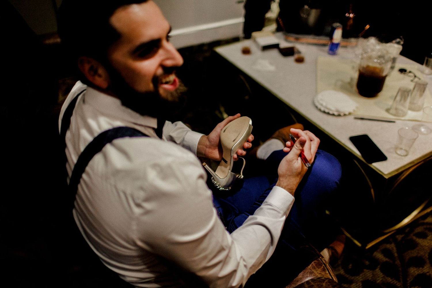 groom writing a special message for bride on shoe
