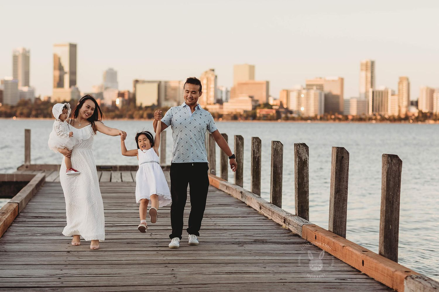 An asian family of four walking along a jetty in South Perth at sunset for a photo shoot